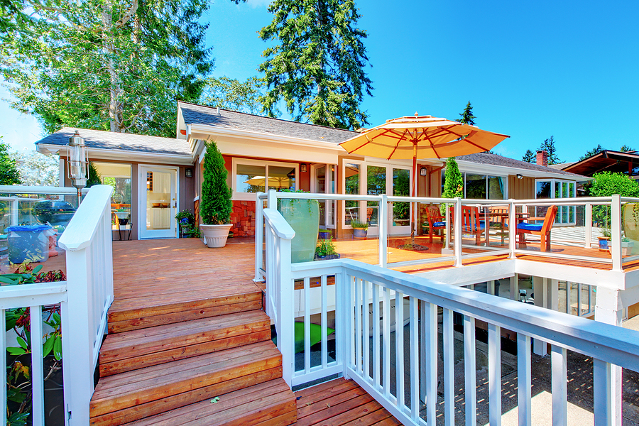 House exterior. Cozy screened walkout deck with patio area and white railings staircase.