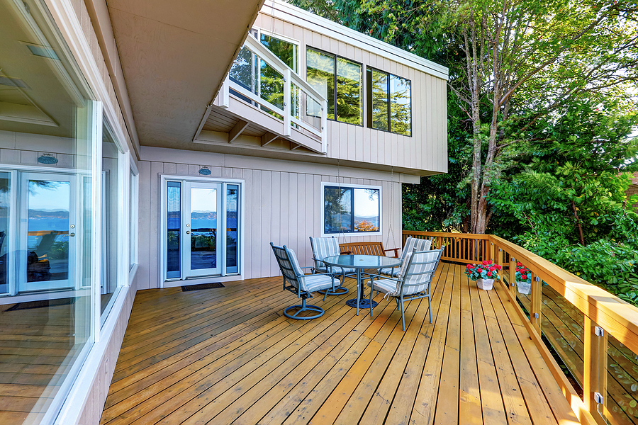 Wooden walkout deck with outdoor table set and swinging bench. Modern beige house exterior. Northwest USA